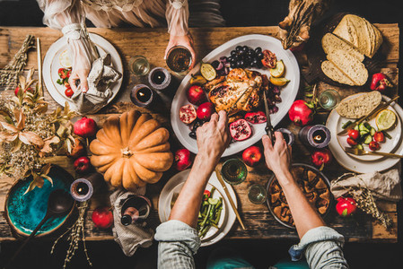 People eating festive dinner on Thanksgiving day with cat