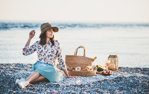 Young woman having weekend picnic at seaside and smiling
