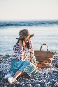 Young woman having picnic at sunset at seaside