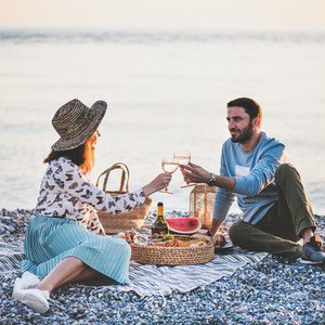Young happy couple having picnic with sparkling square crop
