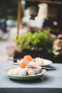 Fresh vegan rice paper summer rolls on table in cafe