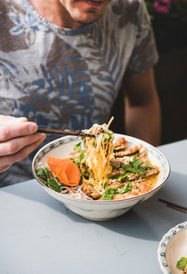 Man eating vietnamese noodle curry with duck from porcelain plate