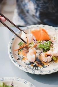Man eating vietnamese Dim Sum dumplings with chopsticks from plate