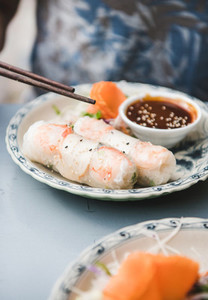 Man eating rice paper summer rolls with chopsticks in cafe