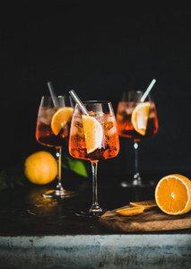 Aperol Spritz cocktail in glass with oranges black background