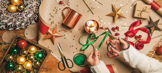 Hot chocolate womans hands with Christmas decoration and scissors