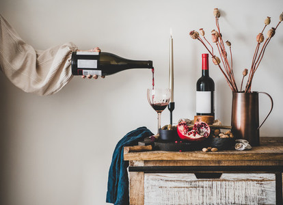 Womans hand pouring wine to glass and set of snacks