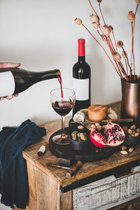 Hand pouring wine from bottle and set of wine snacks