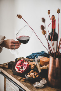Womans hand with glass of red wine over appetizers