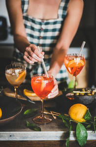 Young woman mixing ingredients in Aperol spritz drink