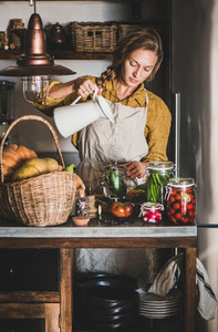 Young blond woman in apron making homemade vegetable preserves