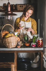 Young blond woman in linen apron making homemade vegetable preserves