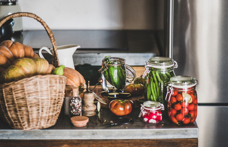 Fresh ingredients and glass jars with homemade vegetables preserves close up