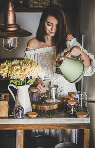 Young woman brewing tea in glass pot at kithcen counter