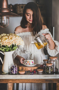 Young smiling woman pouring tea from glass pot into cup