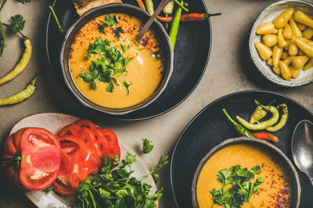 Flat lay of Turkish lentil soup Mercimek with parsley in bowls