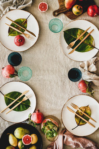 Autumn table setting with seasonal fruits and fallen leaves