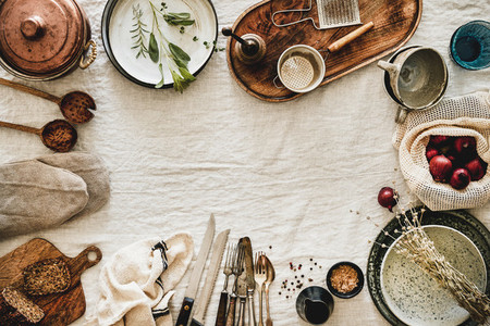 Various kitchen utensils and tablewear over linen tablecloth copy space