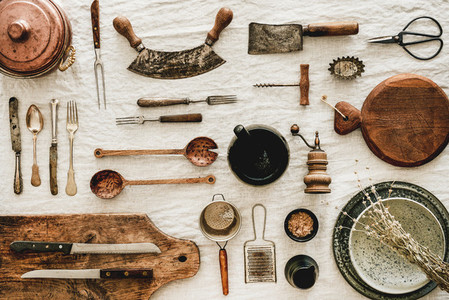 Various kitchen utensils and tablewear over rustic linen tablecloth