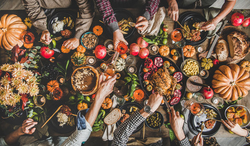People eating and pouring wine at Thanksgiving celebration dinner table