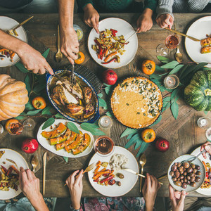 Friends feasting at Thanksgiving Day table with turkey  square crop