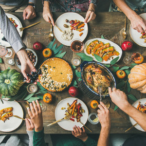 Friends eating at Thanksgiving Day table with turkey square crop