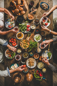 Flat lay of Turkish breakfast and peoples hands with food