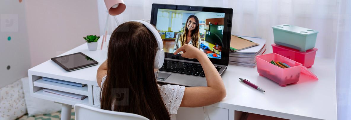 Girl at home receiving online class from her teacher