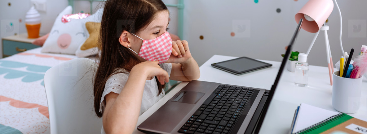 Little girl with mask using laptop