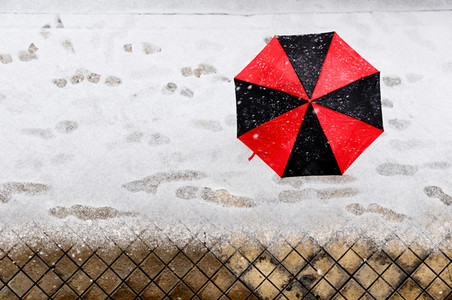Woman holding a black and red umbrella under snow