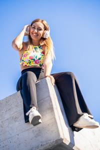 Young woman looking at camera wearing headphones