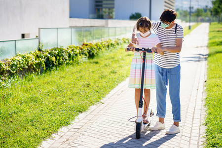Mother teaching her daughter to ride an electric scooter