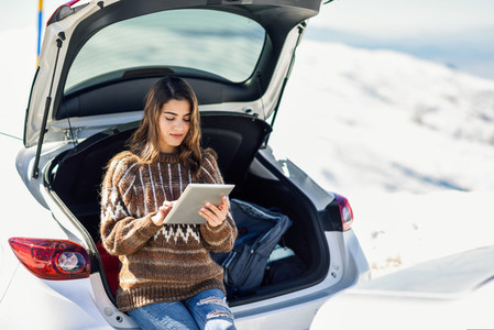 Young traveler woman using digital computer in snowy mountains in winter