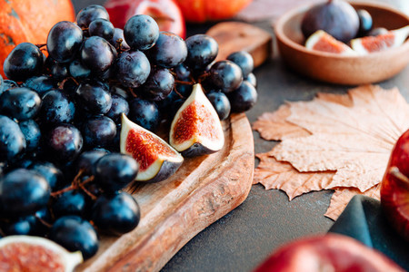 Autumn food red apples figs grapes and pumpkin