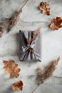 Top view of wrapped gifts by linen fabric in furoshiki eco style with Autumn decor Thanksgiving or Halloween celebration concept