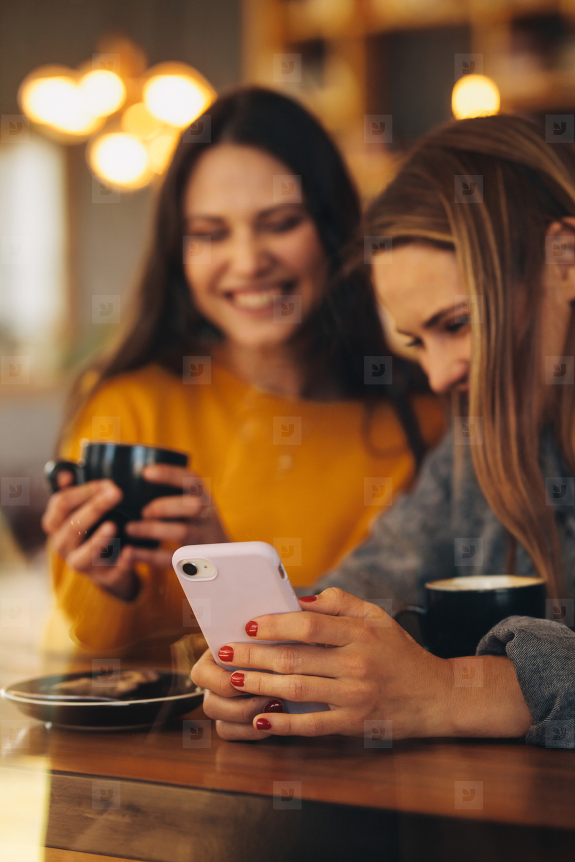 Friends using a smart phone at coffee shop