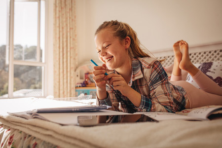 Smiling girl doing homework on bed at home