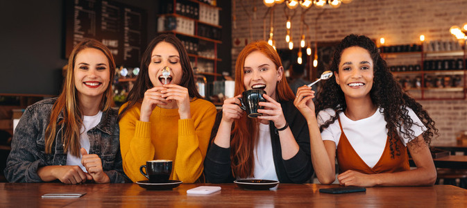 Crazy female friends hanging out at a cafe