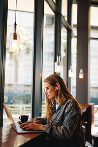 Woman at cafe working on laptop