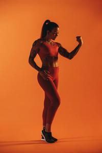 Woman bodybuilder looking at her biceps