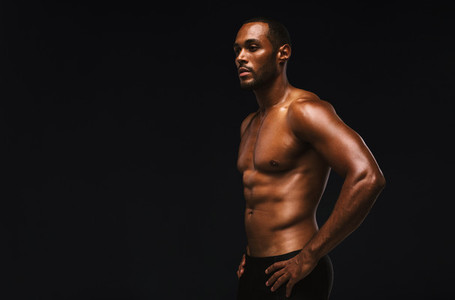 Fit muscular man against black background