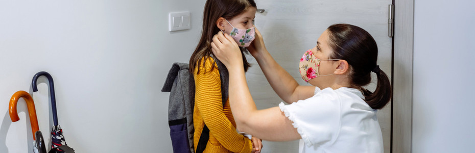 Mother putting the mask on her daughter