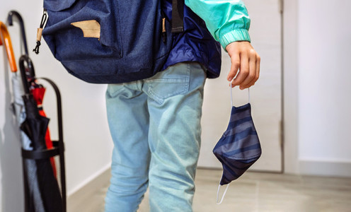 Unrecognizable boy with backpack holding mask in hand
