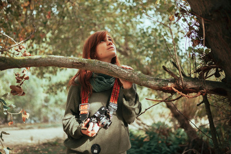 Young woman observing the forest with an old camera
