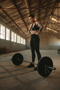 Female exercising with heavy weights inside old warehouse