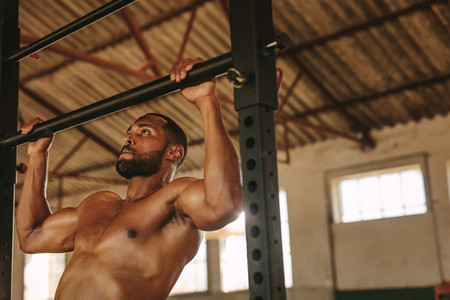 Fit man doing pull up workout inside old warehouse