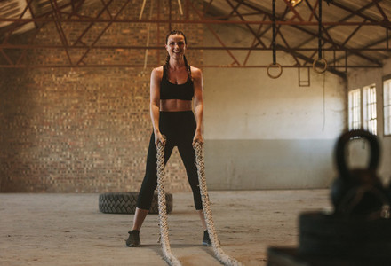 Woman with battling rope in old warehouse