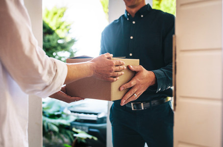 Woman receiving parcel from delivery man