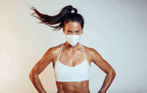Muscular sportswoman with face mask