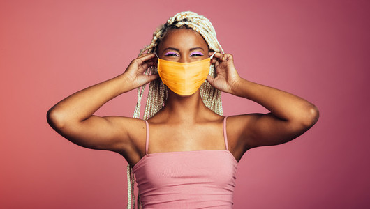 Smiling african woman wearing protective face mask